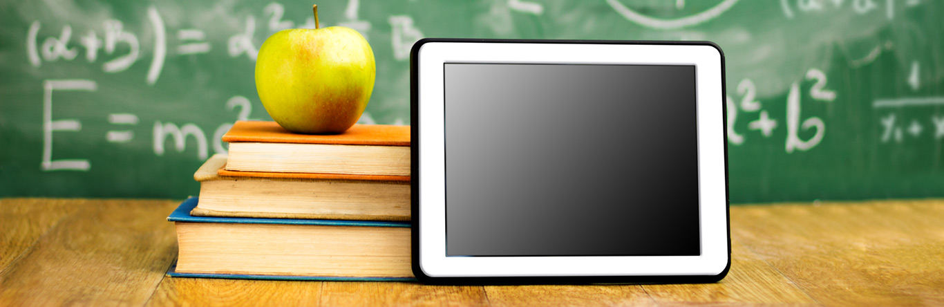Green apple on 3 books next to a tablet in front of a chalk board